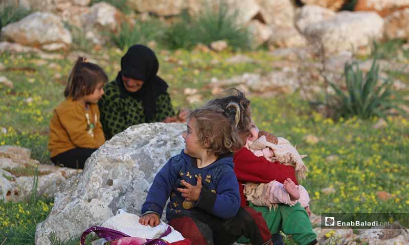 أطفال نازحون بصحبة أمهاتهم في مخيمات باريشا، اللاتي يجمعن حشائش الخبيزة والدردار من براري الحبل لإعدادها للطعام - 13 آذار 2020 (عنب بلدي)