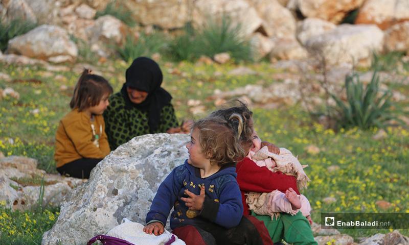 أطفال نازحون بصحبة أمهاتهم في مخيمات باريشا، يجمعون حشائش الخبيزة والدردار من براري الحبل لإعدادها للطعام - 13 آذار 2020 (عنب بلدي)