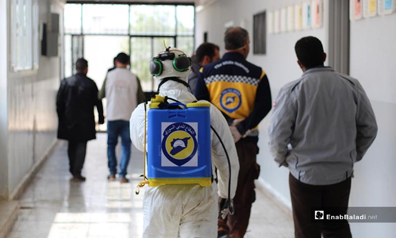 عناصر الدفاع المدني وهم يتجولون في ممرات إحدى مدارس بلدة دابق شمالي حلب لتعقيمها من الفيروس- 29 من آذار (عنب بلدي)