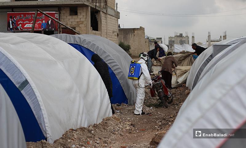 عنصر الدفاع المدني يعقم مابين خيم النازحين في بلدة دابق شمالي حلب- 29 من آذار (عنب بلدي)
