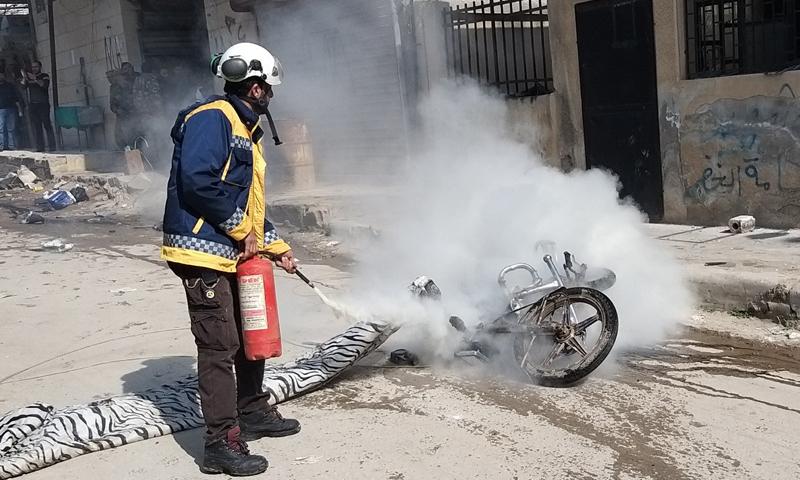 عنصر في الدفاع المدني يطفئ نار اشتعلت بدراجة نارية تنيجة انفجار عبوة ناسفة بالقرب منها وسط عفرين - 8 من آذار 2020 (الدفاع المدني)