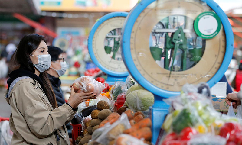 متسوقون يرتدون كمامات للوقاية من فيروس كورونا في سوق في آلما كازاخستان-رويترز