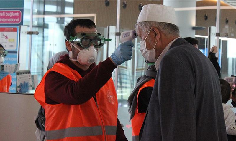 فحص مواطن تركي عائد من العمرة في إحدى المطارات التركية-(الأناضول)