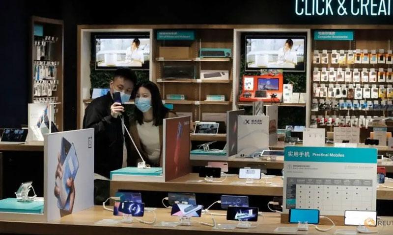صينيون يرتدون الكمامات الطبية في أحد متاجر الهواتف الذكية 25 من آذار 2020 (رويترز)