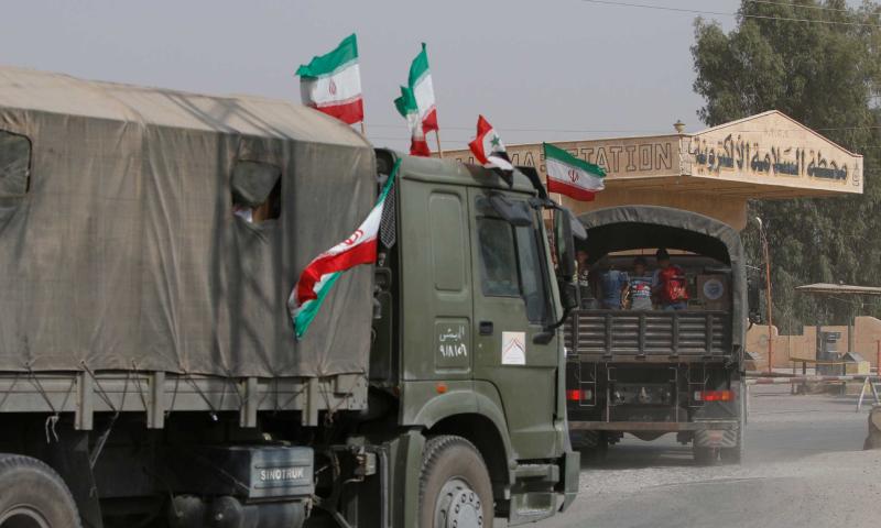 مركبات تحمل العلم الإيراني في دير الزور السورية (رويترز)