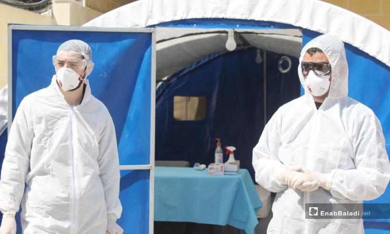 """أعضاء الكادر الطبي لمشفى كفرتخاريم بانتظار المرضى لفرزهم حسب الحالات المرضية وتوجيه تعليمات للوقاية من فيروس """"كورونا"""" ضمن المشفى - 27 آذار 2020 (عنب بلدي)"""