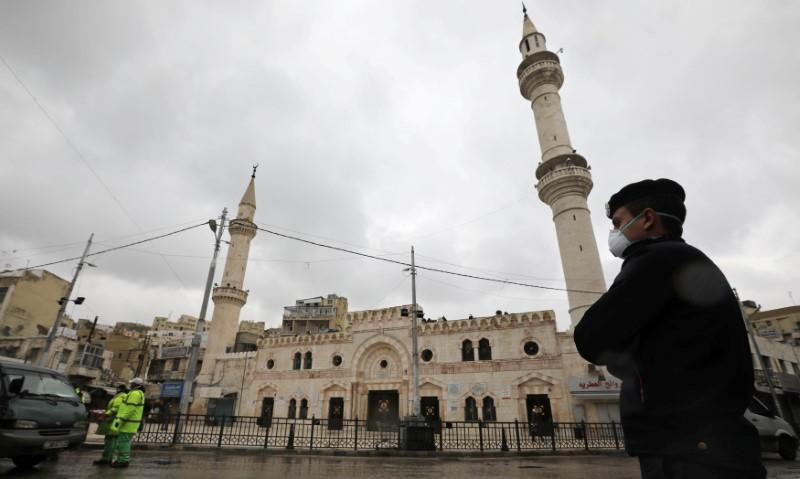 شرطي يضع كمامة في عمان(رويترز)