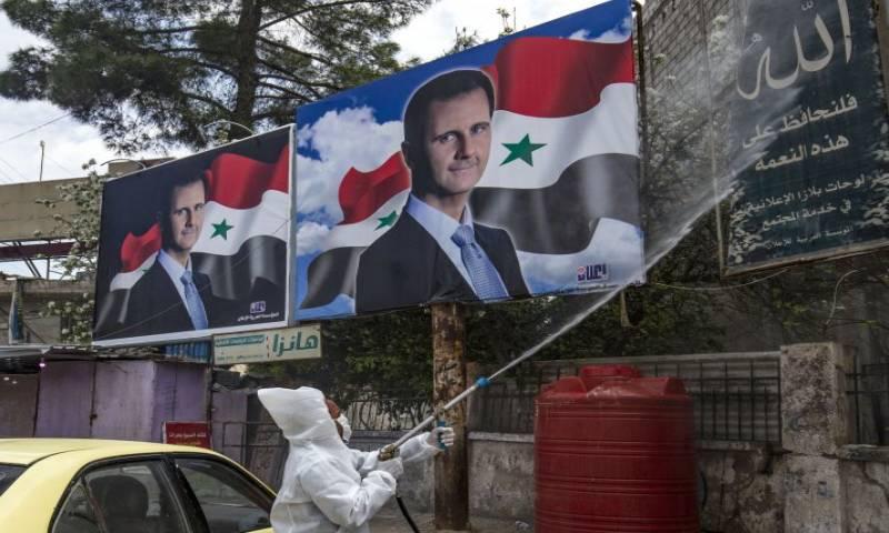عضو من وحدات التطهير التابعة للإدارة الكردية السورية شبه المستقلة يرش اللوحات الإعلانية في القامشلي في 24 من آذار لعام 2020 - (New Stateman)