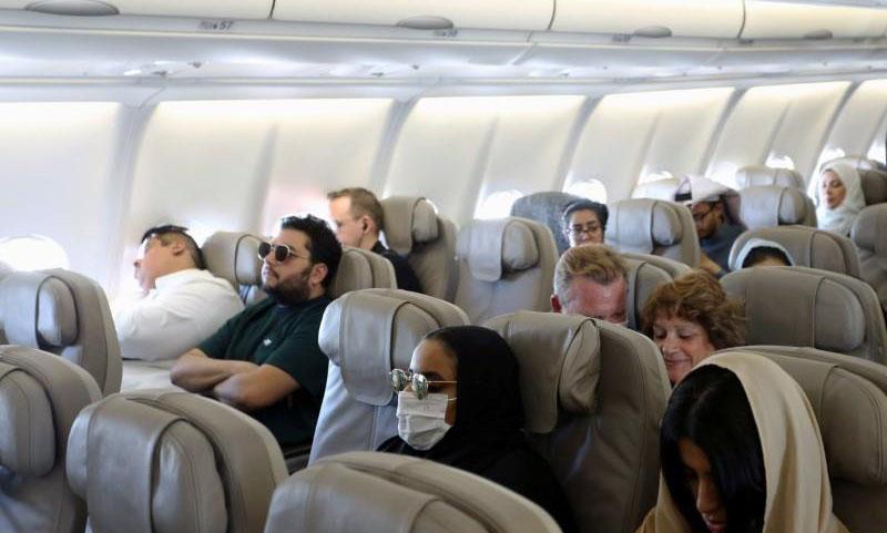 ركاب يضعون كمامات على وجوههم للوقاية من فيروس كورونا على متن طائرة تابعة لشركة الخطوط الجوية السعودية 2020 (رويترز)