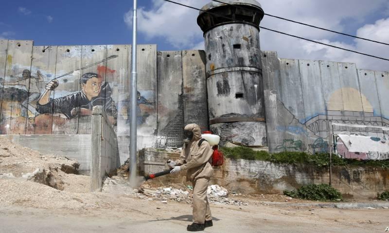 """عامل في إدارة الصرف الصحي الفلسطيني يرش مطهرًا حول مخيم """"عايدة"""" للاجئين في بيت لحم، الذي ظل مغلقًا منذ أكثر من أسبوع بسبب فيروس """"كورونا المستجد"""" 16 من آذار 2020 - (فرانس برس)"""