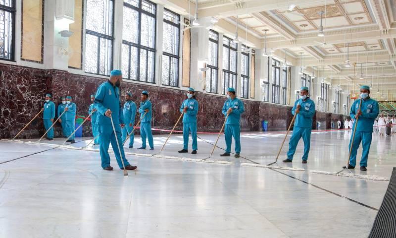 """عمال نظافة يضعون كمامات للوقاية من فيروس """"كورونا المستجد"""" بالمسجد الحرام بمدينة مكة المكرمة 3 من آذار 2020 - (رويترز)"""