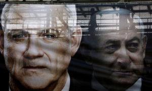 لافتة عليها صورة تجمع رئيس الوزراء الإسرائيلي بنيامين نتنياهو وخصمه الرئيسي بيني جانتس، زعيم حزب أزرق أبيض قبل الانتخابات الأخيرة في شارع بتل أبيب في إسرائيل- 17 شباط 2020 (رويترز).