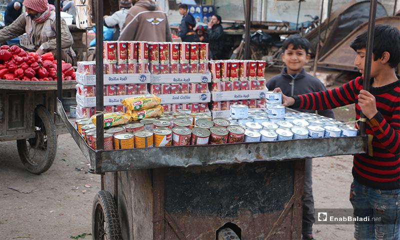 طفل يبيع منتجات معلبة على عربته في سوق مدينة إدلب- 7 من نيسان (عنب بلدي)
