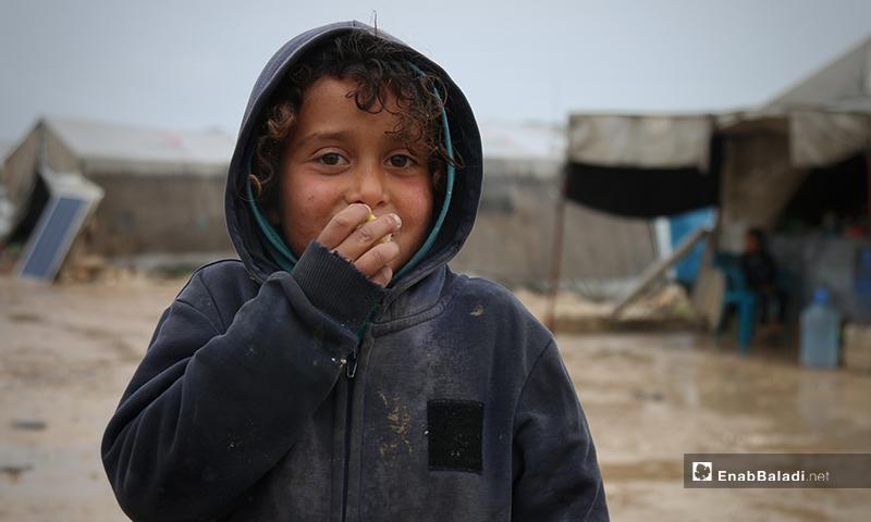 طفل بمخيم حلب لببيه يأكل الطعام في الأجواء الماطرة- 24 من نيسان (عنب بلدي)