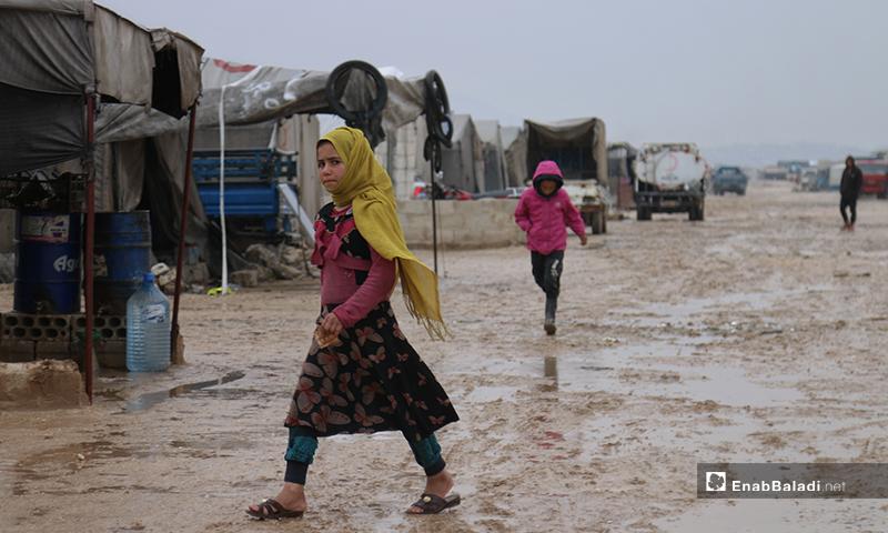 طفلة في مخيم حلب لبيه تسير أثناء المطر في اليوم الأول من رمضان- 24 من نيسان (عنب بلدي)