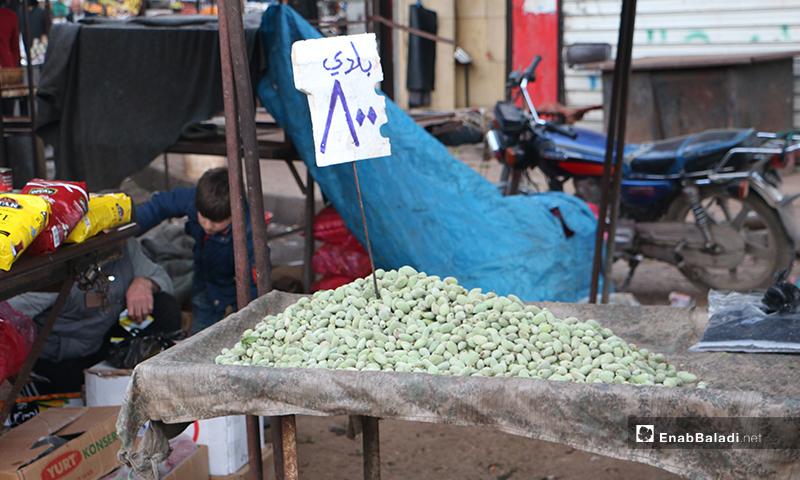 صورة لعربة لوز أخضر في سوق مدينة إدلب- 7 من نيسان (عنب بلدي)
