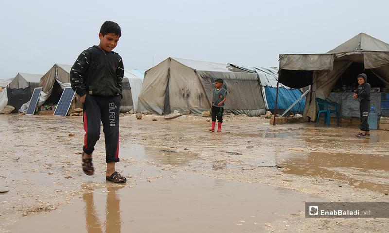 طفل يسير وسط مياه الأمطار التي تتركز في مخيم حلب لبيه- 24 من نيسان (عنب بلدي)