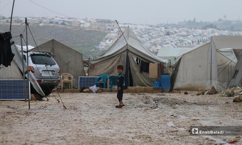 طفل يقف أمام خيمات في مخيم حلب لبيه، خلال اليوم الأول من رمضان- 24 من نيسان (عنب بلدي)