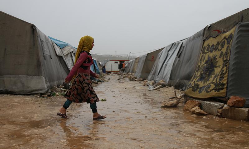 طفلة تسير بين اخيم بمخيم حلب لبيه أثناء الأجواء الماطرة باليوم الأول من رمضان- 24 من نيسان (عنب بلدي)