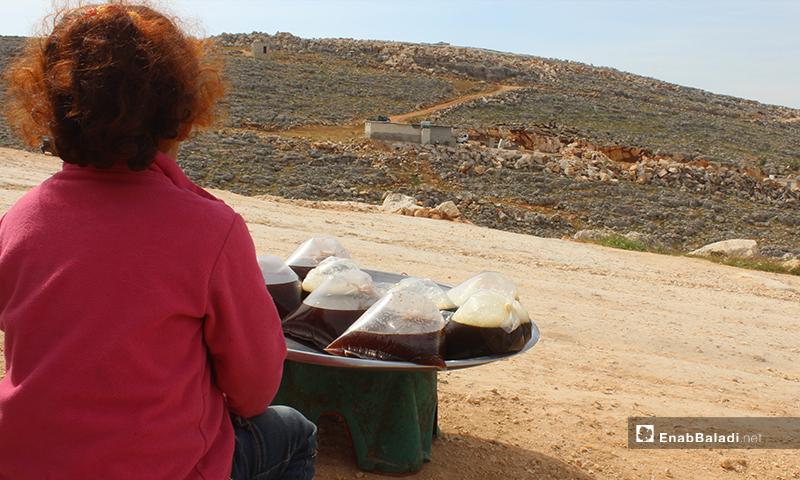 تجلس تيماء ذات الأربع سنوات على قارعة طريق المخيمات بالقرب من مدينة سرمدا