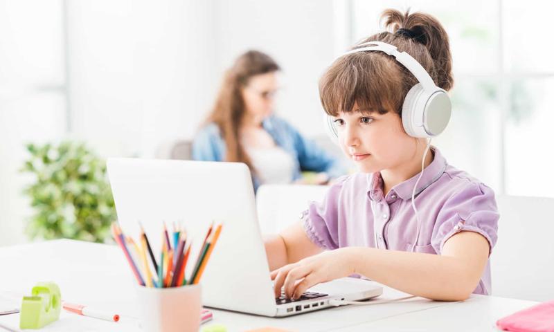 طفلة تتعلم عبر الإنترنت وخلفها والدتها- (123rf)