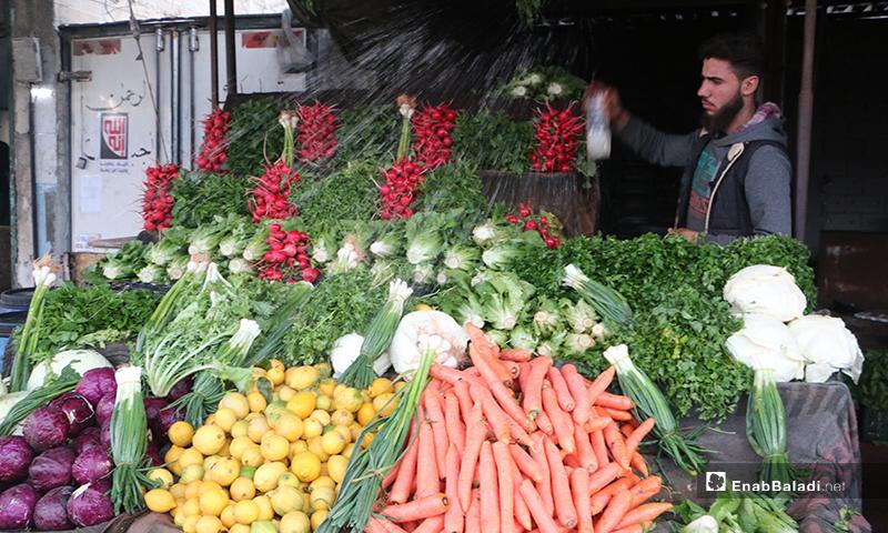 بائع يرش الماء على الخضروات في سوق مدينة إدلب- 7 من نيسان (عنب بلدي)