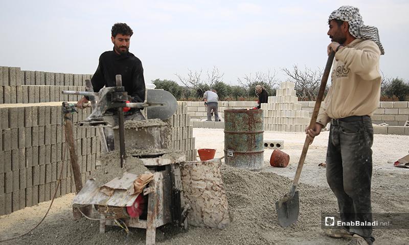 عاملان سوريان يعملون على بناء وحدات سكنية أسمنتية عوضًا عن الخيام للنازحين في مخيمات في الشمال السوري- 15 من نيسان 2020 (عنب بلدي)