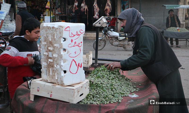 رجل يشتري لوز أخضر من طفل يبيعه على عربته في سوق مدينة إدلب- 7 من نيسان (عنب بلدي)