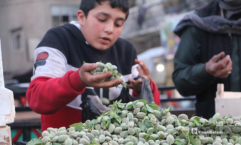 طفل يبيع لوز أخضر على عربته في سوق مدينة إدلب- 7 من نيسان (عنب بلدي)