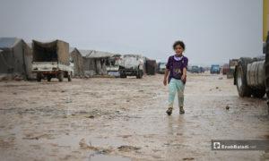 طفلة تسير وسط مخيم حلب لبيه في الأجواء الماطرة باليوم الأول من رمضان- 24 من نيسان (عنب بلدي)
