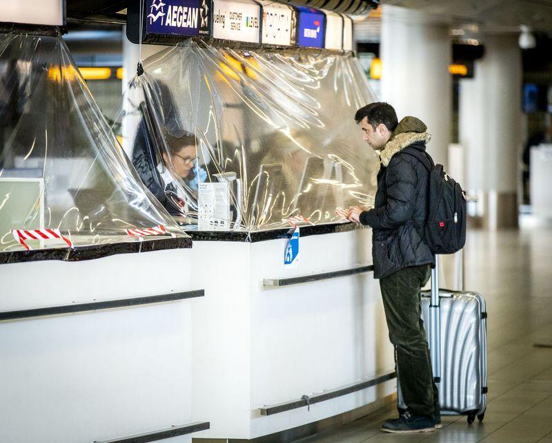 مسافر أمام كابينة لشركة طيران محمية بمواد بلاستيكية مشمع في مطار شيفول في أمستردام- 27 من آذار (بلومبيرغ).