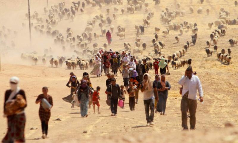 مجموعة من الأقلية الأزيدية تهرب باتجاه الحدود السورية مع دخول تنظيم الدولة الإسلامية إلى سنجار (رويترز)