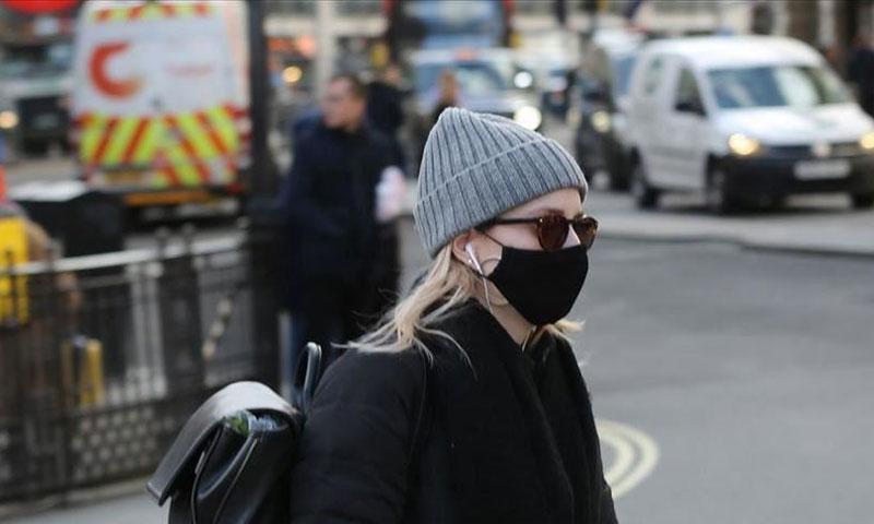 امرأة ترتدي الكمامة الطبية للوقاية من الكورونا في بريطانيا (الأناضول)