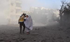 عنصر من الدفاع المدني يبعد سيدة وطفلتها من مكان قصف النظام وروسيا - آذار 2020 (الدفاع المدني)
