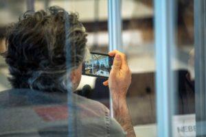 شاهد سوري يصور جلسة محكمة ألمانية في كوبلنس لمقاضاة الضابطين السوريين أنور رسلان وإياد الغريب بارتكاب جريمة ضد الإنسانية - 23 نيسان 2020 (AFP)