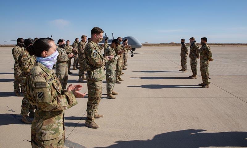 أفراد من الجيش الأمريكي يرتدون الأقنعة ويمارسون التباعد الجسدي للوقاية من COVID-19 أيار (DOD)