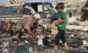 طفل صغير ورجل مسن يبحثون عما لم يحرق من خيمتهم في مخيم دير حسان التابع للدانا في ريف إدلب الشمالي- 17 من أيار (يوسف غريبي/عنب بلدي).