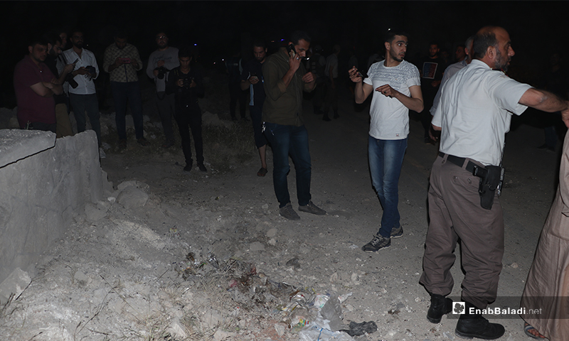 عناصر من الشرطة تبعد مدنينن عن مكان انفجار عبوة ناسفة لمعاينته - 14 أيار 2020 (عنب بلدي/ عاصم ملحم)