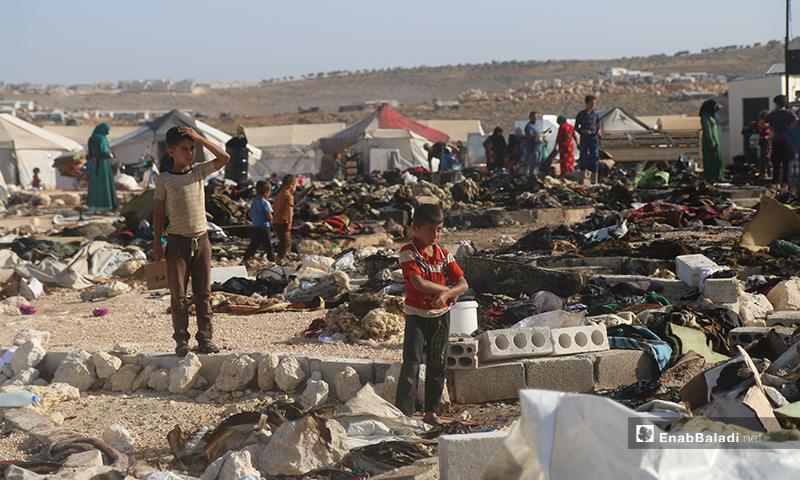 يعاين هذا الطفل أضرار الحريق الذي التهم 60 خمية في مخيمات دير حسان بمنطقة الدانا، مذهولًا من هول ماحدث- 17 من أيار (يوسف غريبي/عنب بلدي).