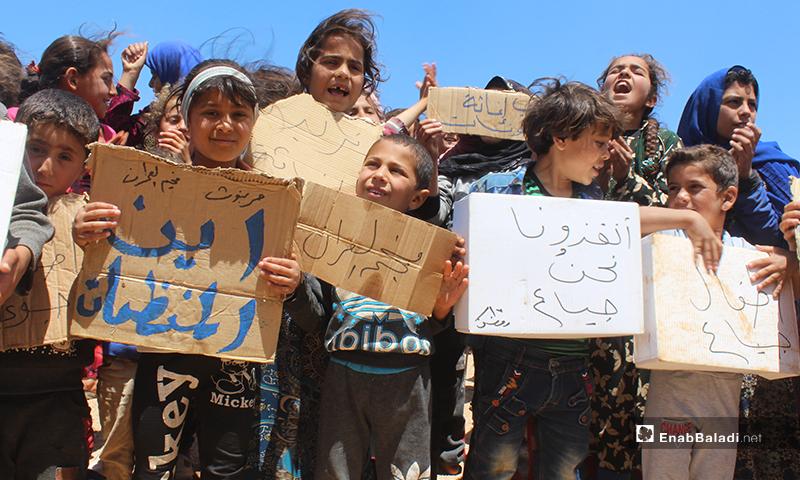 """أطفال يحملون لافتات في مظاهرة مخيم """"العمران"""" غربي حربنوش- 10 من أيار (عنب بلدي)"""
