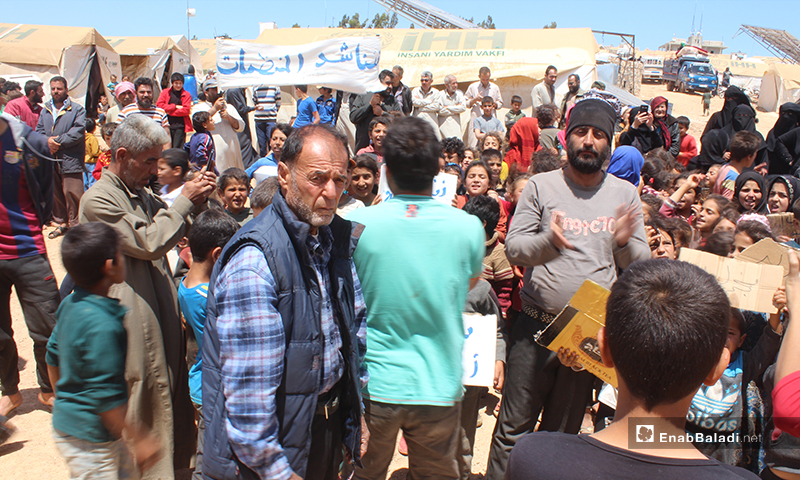 """مظاهرة مخيم """"العمران"""" غربي حربنوش المطالبة بتأمين الحاجات الأساسية من غذاء وماء وخدمات أخرى- 10 من أيار (عنب بلدي)"""