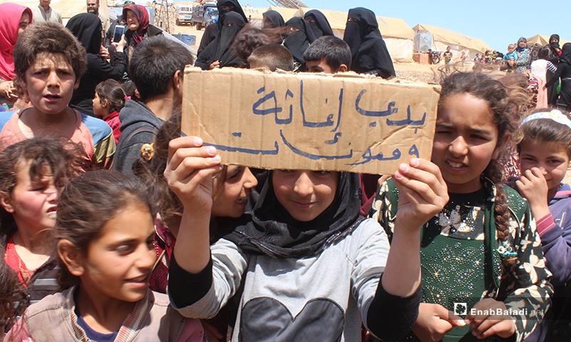 """طفلة تحمل لافتة كتب عليها """"بدي إغاثة ومعونات"""" بمظاهرة مخيم """"العمران"""" غربي حربنوش- 10 من أيار (عنب بلدي)"""
