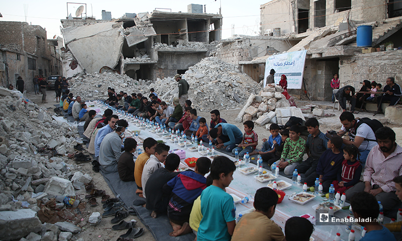 أهالي مدينة الأتارب بريف حلب وهم على مائدة الإفطار الجماعية بين الركام- 8 من أيار (عنب بلدي)