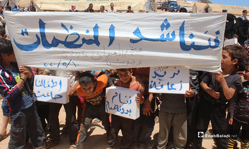 """لافتات مظاهرة نازحي مخيم """"العمران"""" غربي حربنوش المطالبة بالحاجات الأساسية والخدمية- 10 من أيار (عنب بلدي)"""