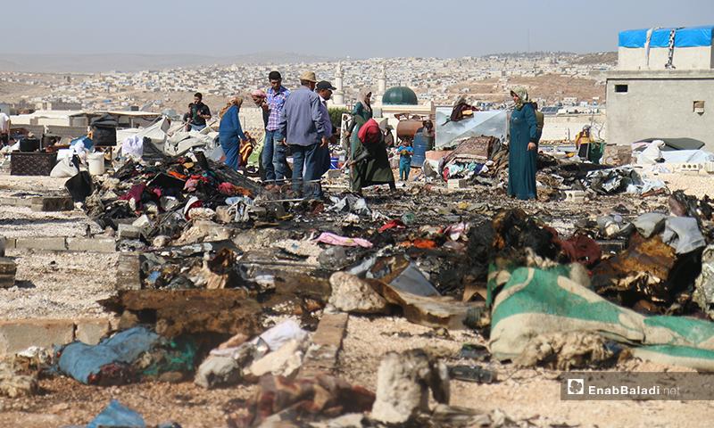 نازحو مخيم دير حسان يبحثون عن أمتعتهم التي لم تتضر، بعد الحريق الذي أصاب خيمهم- 17 من أيار (يوسف غريبي/عنب بلدي).