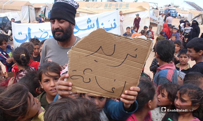 """""""نريد إغاثة"""" لافتة يحملها طفل نازح خلال مظاهرة مخيم """"العمران"""" غربي حربنوش- 10 من أيار (عنب بلدي)"""