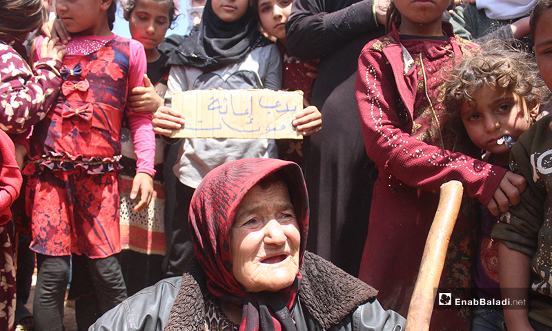 """امرأة مسنة وخلفها أطفال خلال مظاهرة مخيم """"العمران"""" غربي حربنوش- 10 من أيار (عنب بلدي)"""