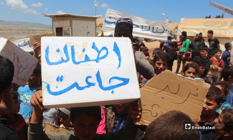 """""""أطفالنا جاعت"""" لافتة يحملها طفل نازح خلال مظاهرة مخيم """"العمران"""" غربي حربنوش- 10 من أيار (عنب بلدي)"""