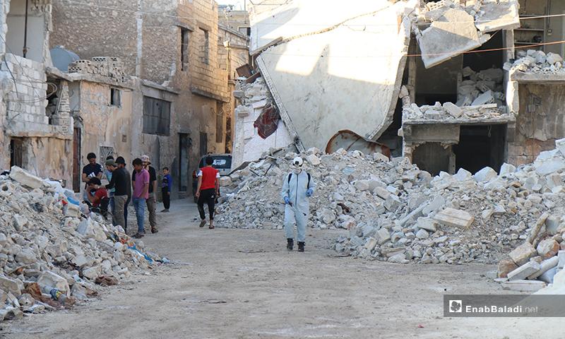 """عنصر من """"الدفاع المدني"""" يعقم المكان الذي تجمع فيه أهالي مدينة الأتارب في ريف حلب  من أجل الإفطار الجماعي- 8 من أيار (عنب بلدي)"""