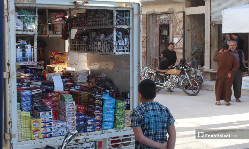 طفل يققف أمام سيارة بيك آب تبيع المنتجات الغذائية في سرمين بريف إدلب الشرقي- 8 من أيار (عنب بلدي)